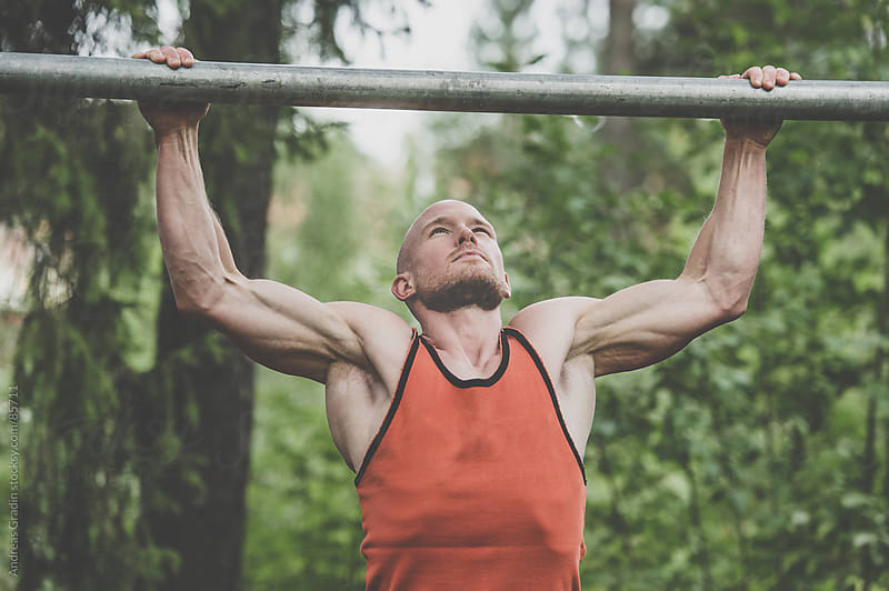 fit male doing pullups by Andreas Gradin for Stocksy United