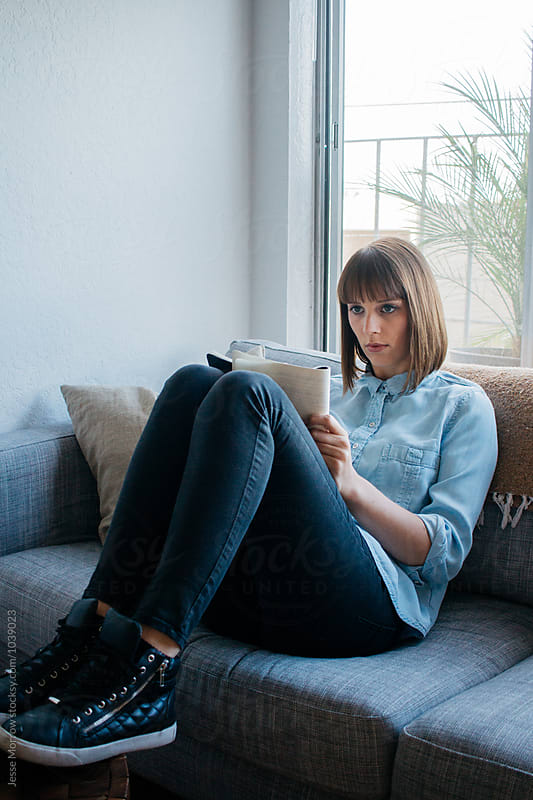 Young female entrepreneur works on business homework study fro home on couch with mobile phone by Jesse Morrow for Stocksy United