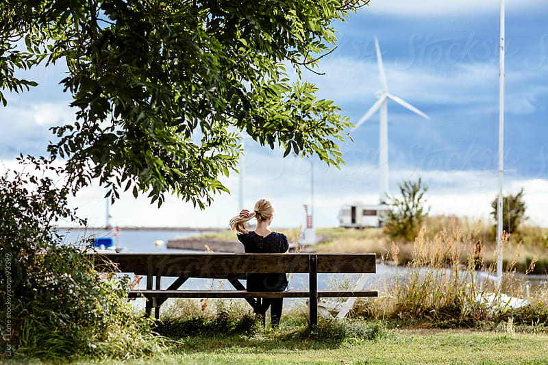 Woman sitting on a bench in a marina by Lior + Lone for Stocksy United