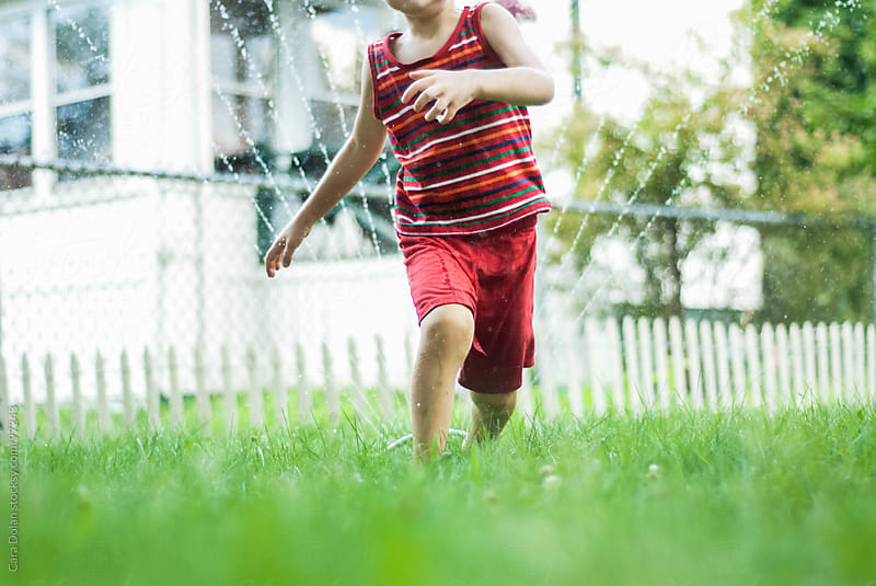 Boy runs through a backyard sprinkler in summertime by Cara Dolan for Stocksy United