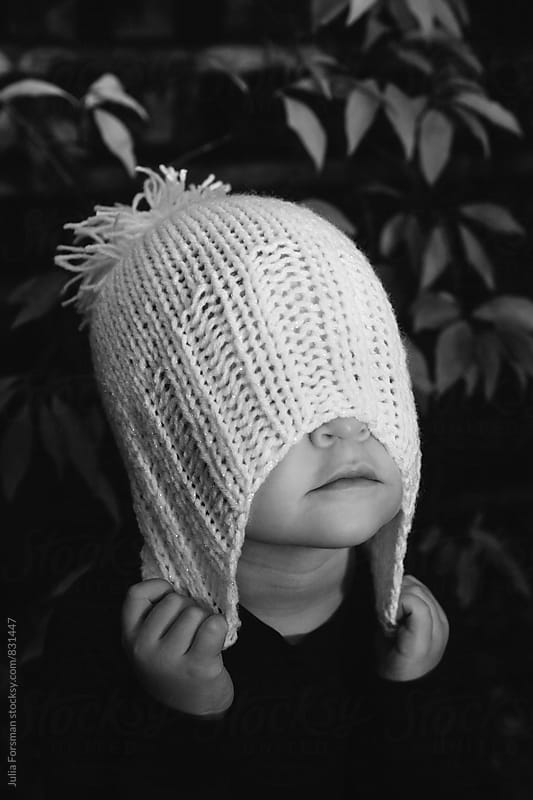 A little girl clasps the woolly hat she is wearing pulling it over her eyes. by Julia Forsman for Stocksy United