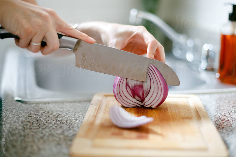Knife cuts through onion by Jennifer Brister for Stocksy United