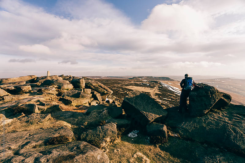 Male with backpack on Stanage Edge at sunset. Derbyshire, UK. by Liam Grant for Stocksy United