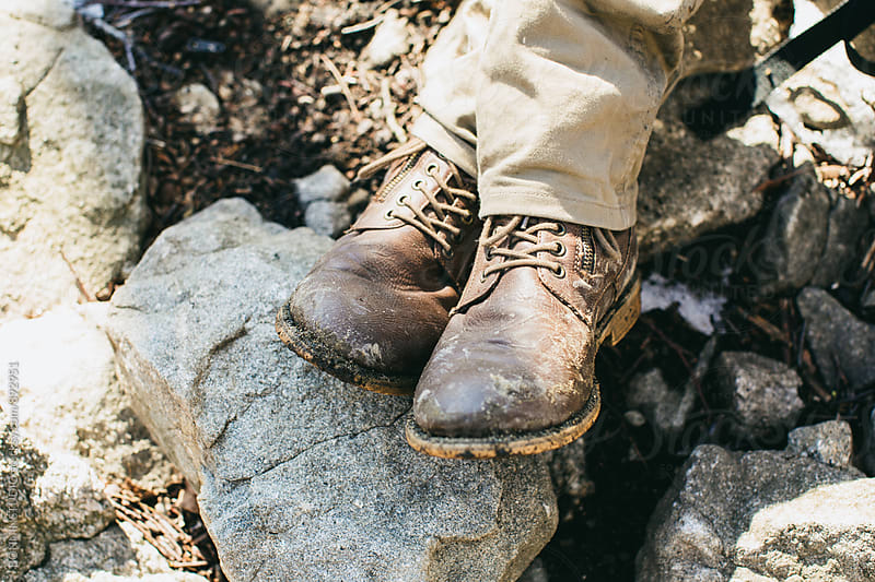 Closeup of a dirty boots on rocks.  by BONNINSTUDIO for Stocksy United