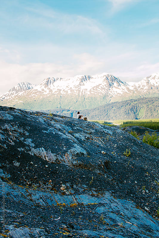 Man Sits On Top Of Rocky Hill Surrounded By Mountains In The Alaska Wilderness by Luke Mattson for Stocksy United