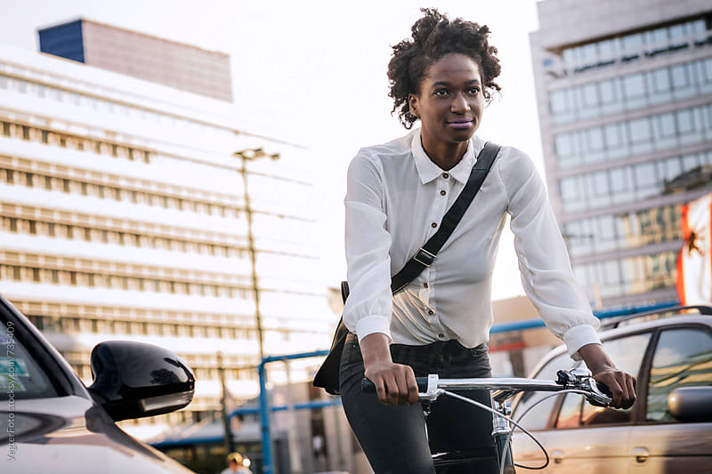 Black woman commuting  to work on Bicycle by VegterFoto for Stocksy United