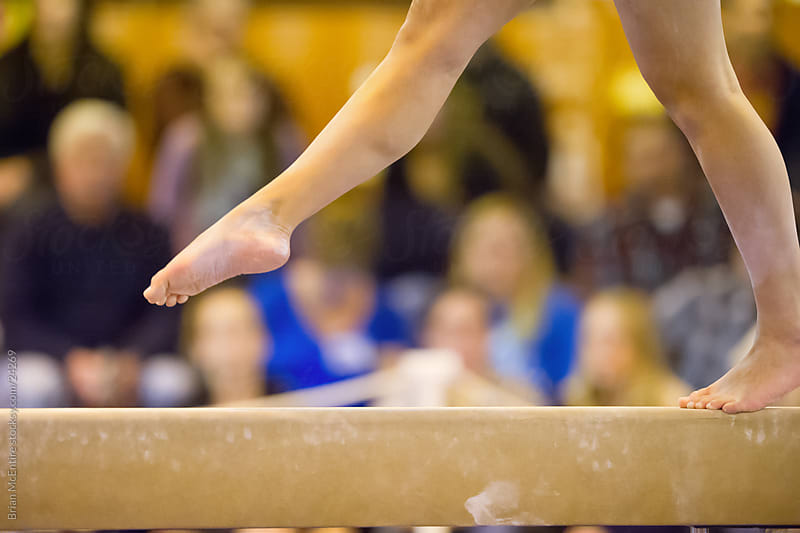 Close-up of Gymnasts feet on beam with crowd in background by Brian McEntire for Stocksy United