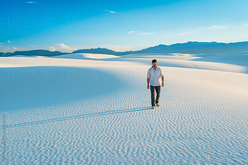 Man Hiking In Sand Dunes with Vibrant Clear Blue Sky in White Sands National Monument New Mexico by JP Danko for Stocksy United
