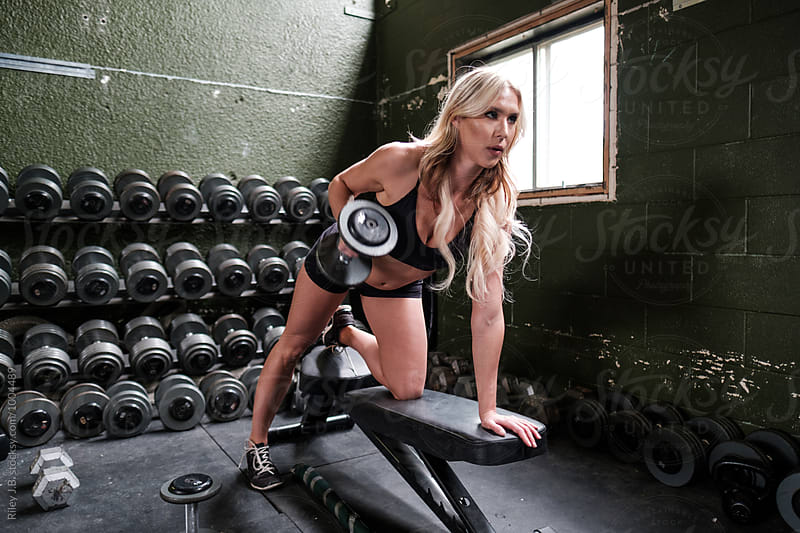 An attractive woman exercises with dumbbell by Riley J.B. for Stocksy United