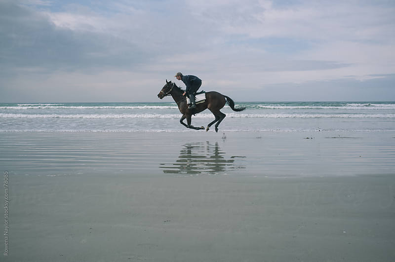 Horse Riding on the beach at sunrise in winter by Rowena Naylor for Stocksy United