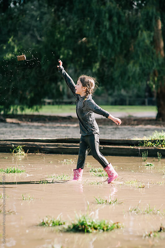 Preschool girl, standing in a puddle, throwing block of wood by Gary Radler Photography for Stocksy United