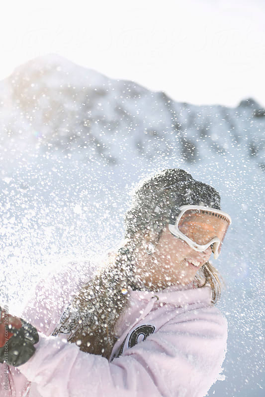 Young woman gets splashed with snow balls by Miquel Llonch for Stocksy United
