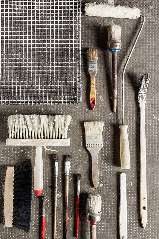 Variety of painting tools on a stone background by Melanie Kintz for Stocksy United
