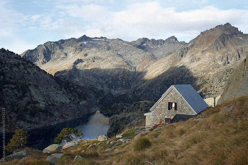 Mountain hut and lake in the beautiful Pyrenees mountains by Miquel Llonch for Stocksy United