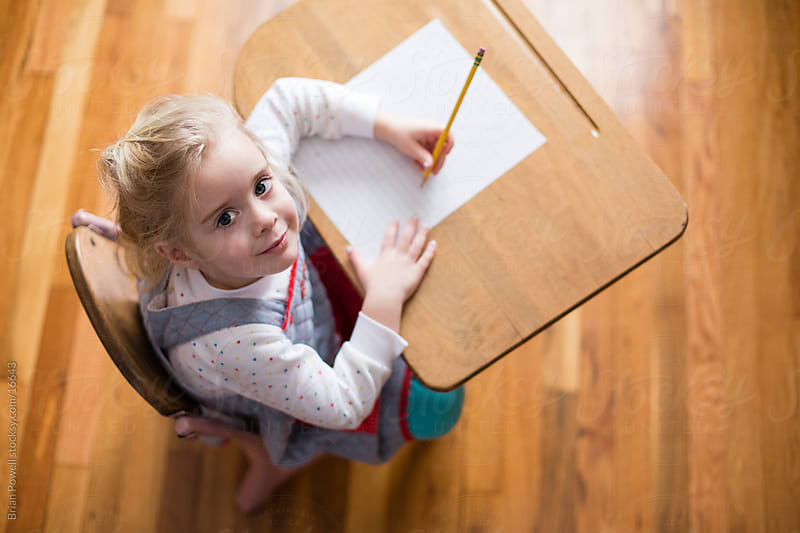 preschool girl looks up from desk by Brian Powell for Stocksy United