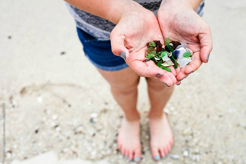 Cupped hands holding multicolored sea glass from the beach in Monterey. by Carolyn Lagattuta for Stocksy United