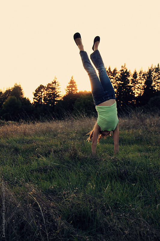 Little girl doing a handstand in an open field with the sun setting through the forest behind her. by Carolyn Lagattuta for Stocksy United