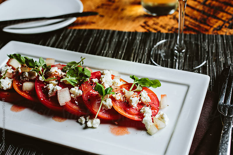 Summer Tomato Salad with micro basil and fresh cheese  by Andrew Cebulka for Stocksy United
