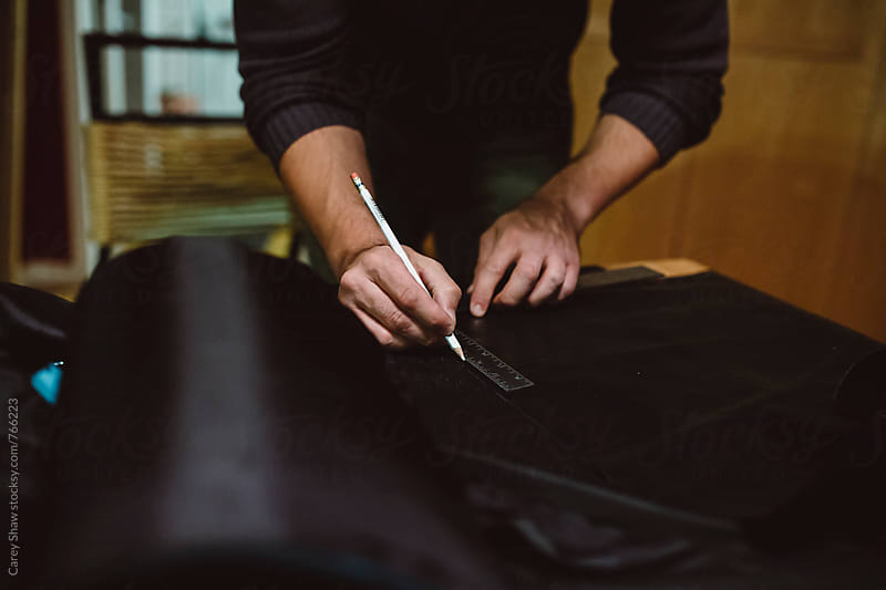 Man marking fabric in studio by Carey Shaw for Stocksy United