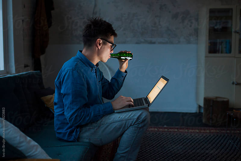 A young entrepeneur or professional working ovetime in his office  on his laptop, during the night by Ivo de Bruijn for Stocksy United