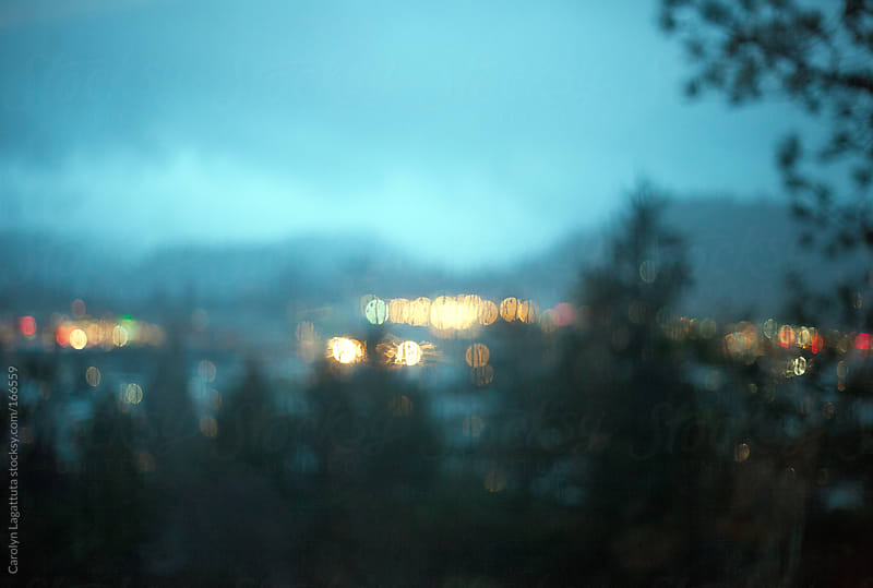 Blurry shot of a storm in a valley of mountains, lights and fog by Carolyn Lagattuta for Stocksy United
