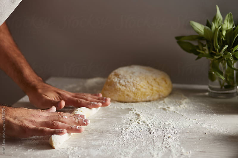 Man rolling dough on table by Martí Sans for Stocksy United