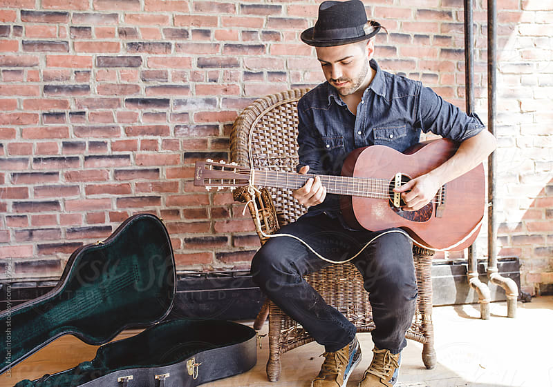 young brazillian man playing guitar, wearing fedora by Lisa MacIntosh for Stocksy United