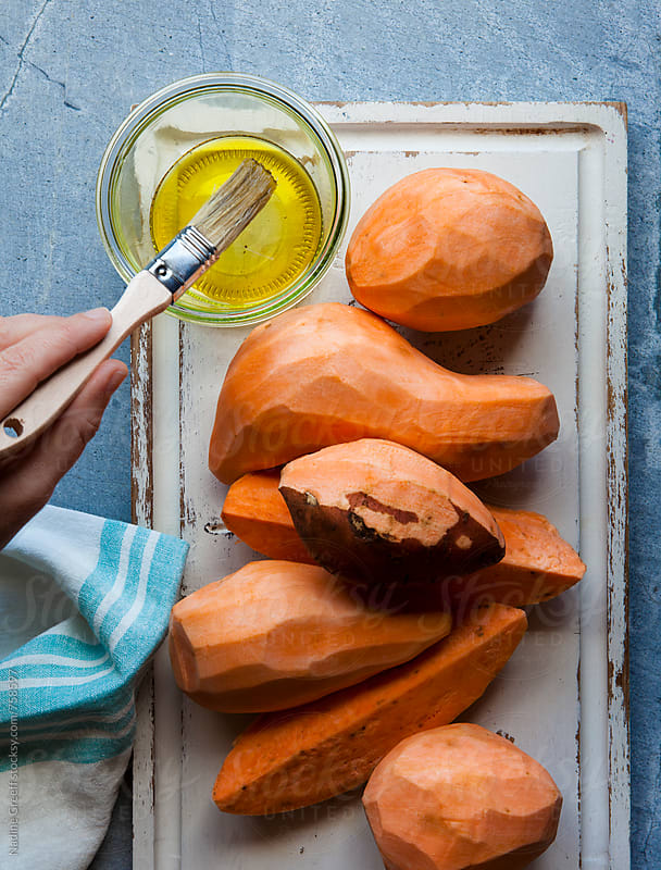 Basting sweet potatoes with olive oil as seen from above by Nadine Greeff for Stocksy United