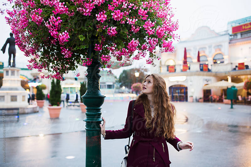 Rainy day; young woman looking at pink flowers by Jovana Rikalo for Stocksy United