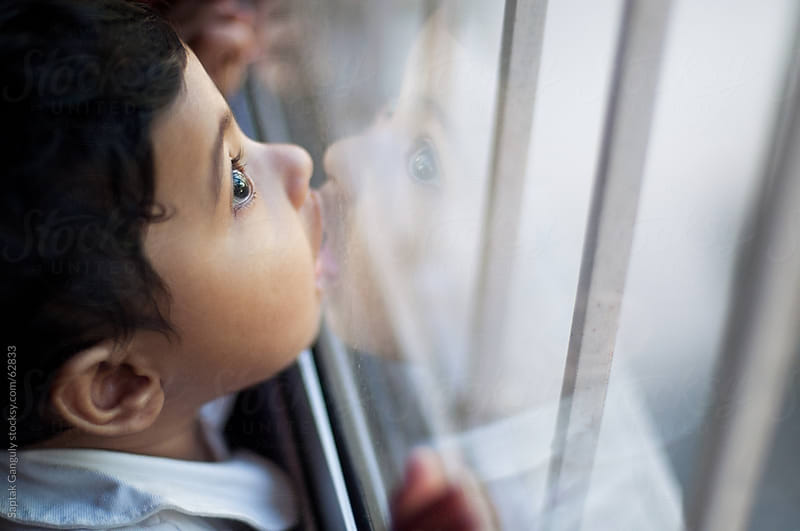 Cute baby girl kissing glass window pane by Saptak Ganguly for Stocksy United