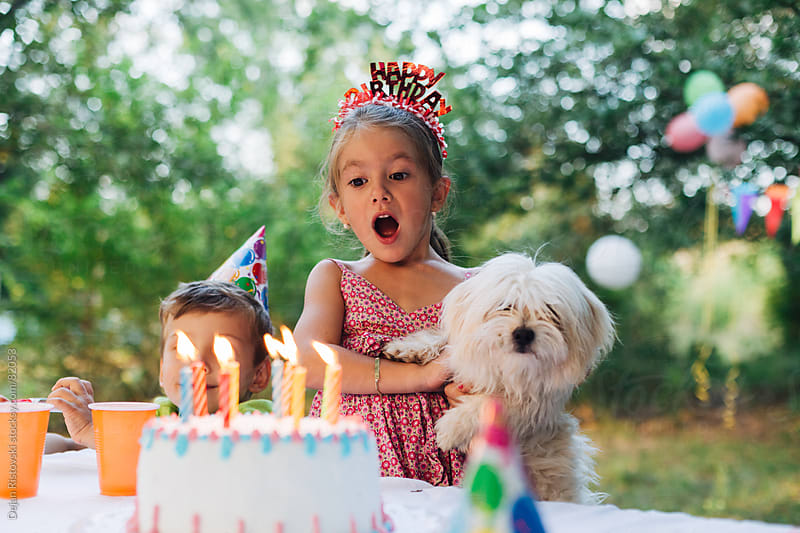 Child blowing her birthday candles by Dejan Ristovski for Stocksy United