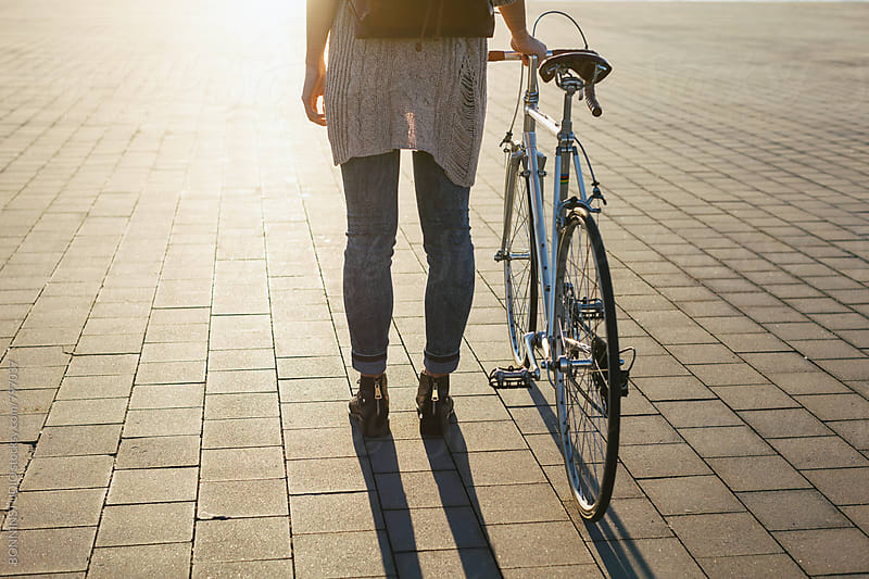 Back view of a woman standing with her vintage bicycle on a sunny day. by BONNINSTUDIO for Stocksy United