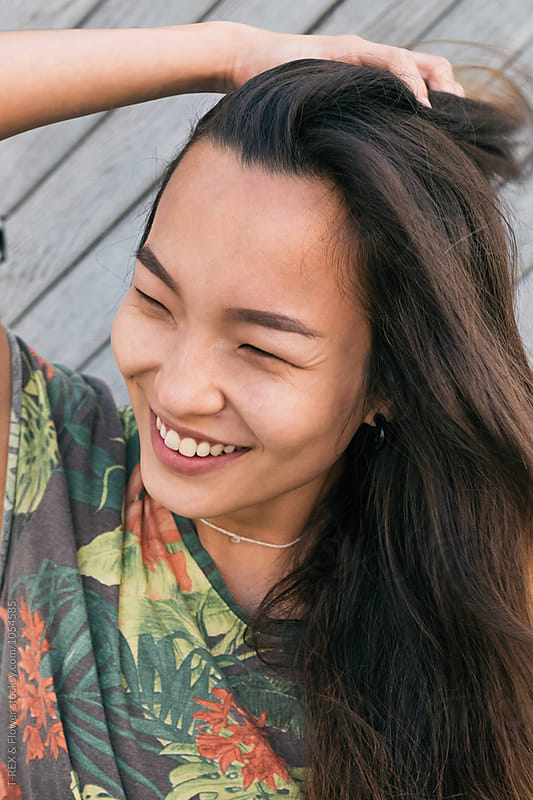Close-up of candid asian girl with squinted eyes holding brunette hair by T-REX & Flower for Stocksy United
