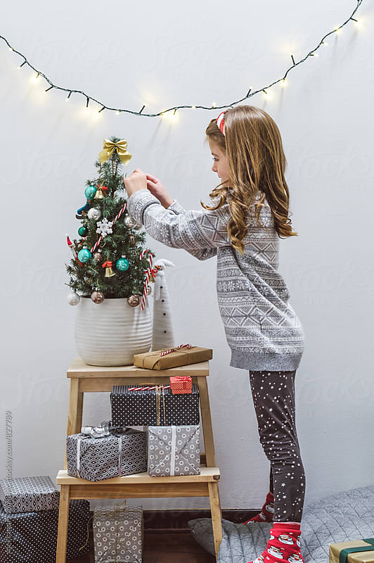 Cute Little Girl Decorating Christmas Tree by Aleksandra Jankovic for Stocksy United