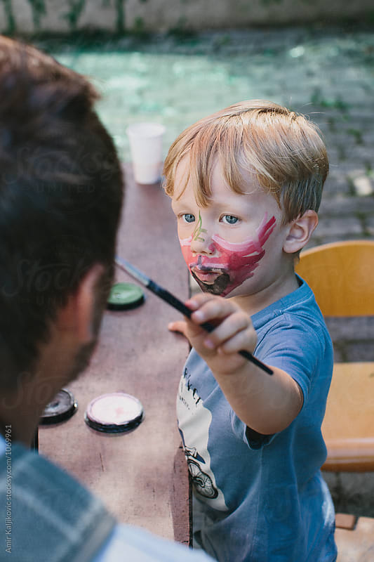 Boy with paintbrush and face paint by Amir Kaljikovic for Stocksy United