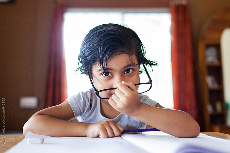Little girl with glasses looking at camera while studying by Saptak Ganguly for Stocksy United