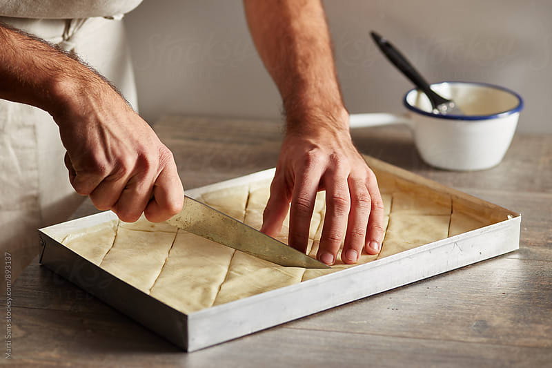 Chef cuts uncooked baklava diagonally with knife by Martí Sans for Stocksy United