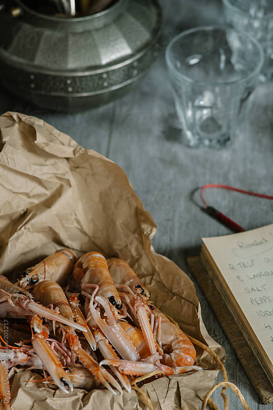 Langoustines on kitchen table with recipe book. by Darren Muir for Stocksy United