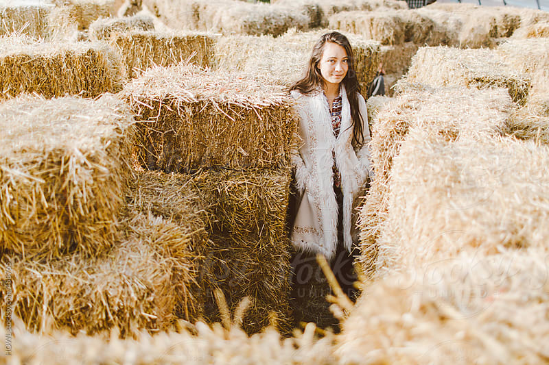 young girl stands among haystacks on a farm  by HOWL for Stocksy United
