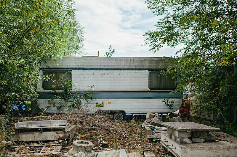 An old caravan surrounded by trees and rubble by kkgas for Stocksy United