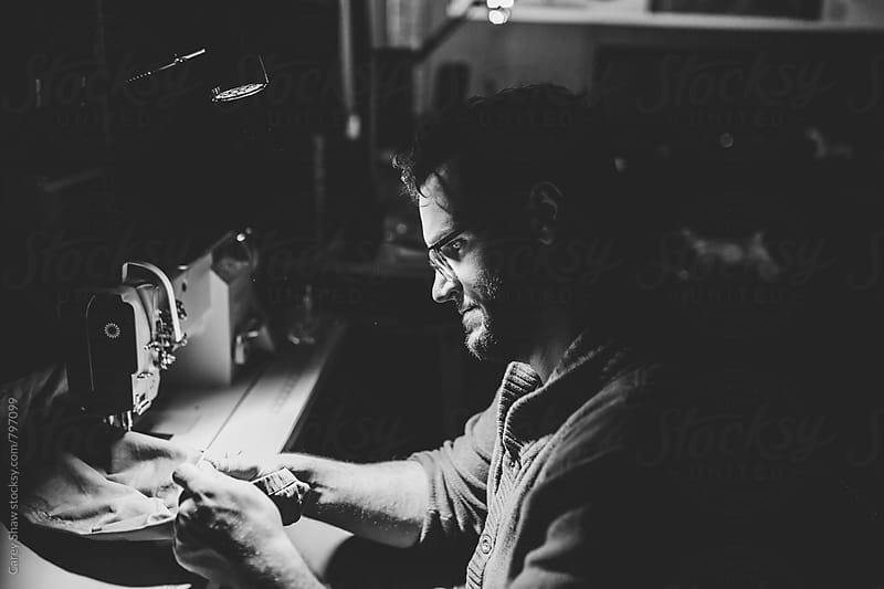 Black and white portrait of man sewing in studio by Carey Shaw for Stocksy United