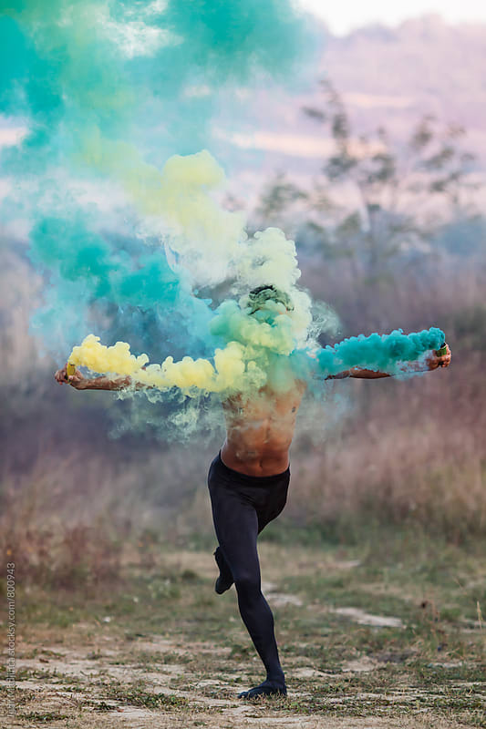 faceles , ballet dancer with two smoke bombs dance in nature by Igor Madjinca for Stocksy United