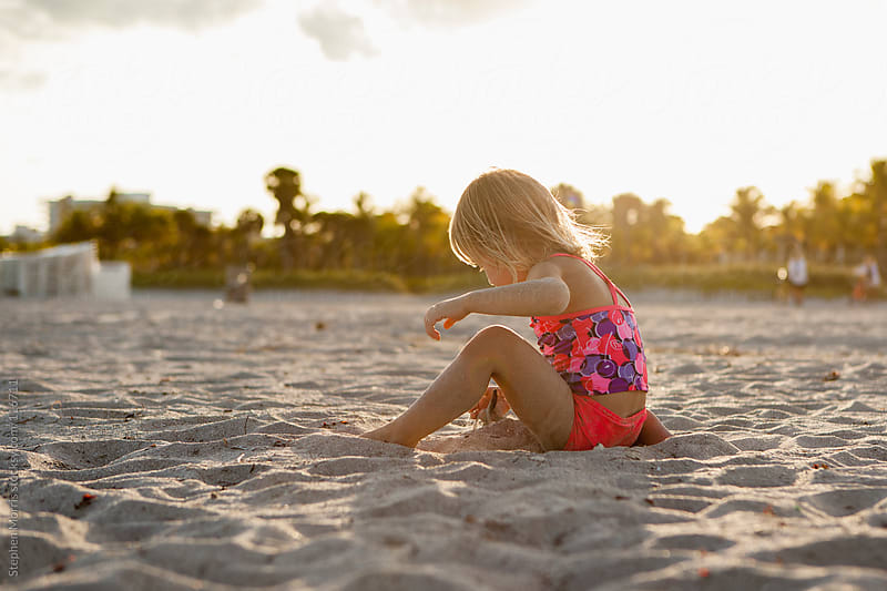 Girl playing in the sand on Beach by Stephen Morris for Stocksy United