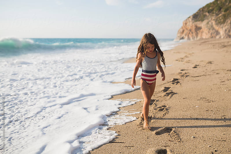 Girl walking trough coastline. by Dejan Ristovski for Stocksy United