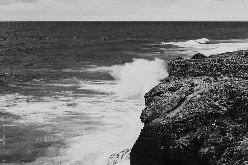 Atlantic ocean waves hitting the rocks black and white by Natasa Kukic for Stocksy United