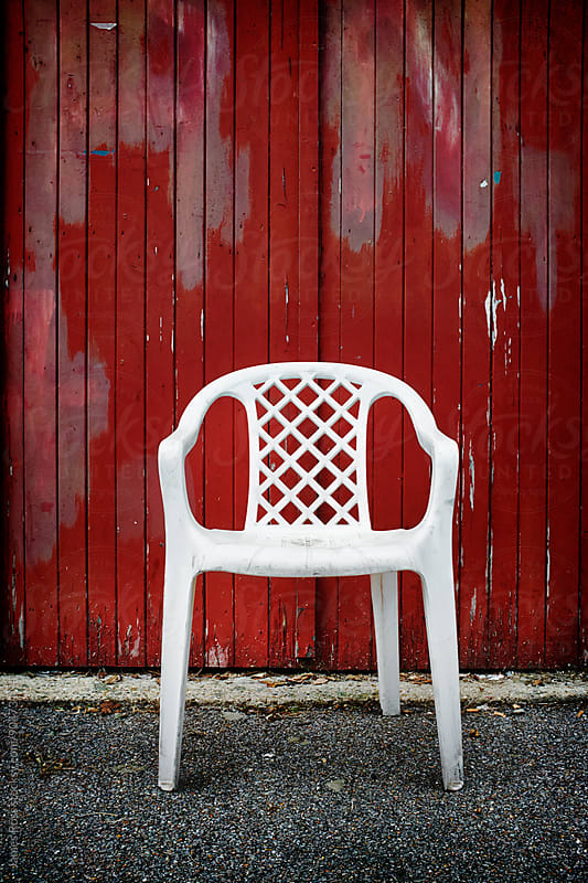 A three legged white plastic chair  by James Ross for Stocksy United