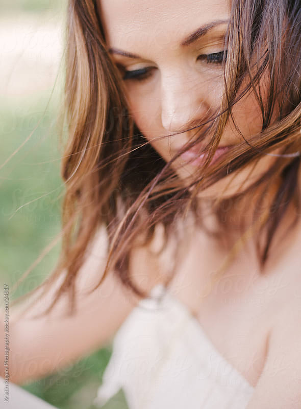 Portrait of woman with wind blown hair by Kristin Rogers Photography for Stocksy United