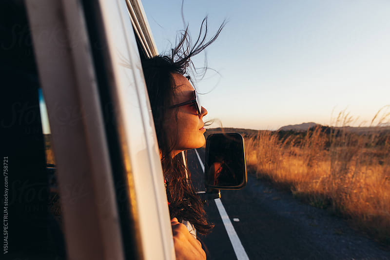Road Tripping - Beautiful Woman Sticking Head Outside Car Window While Driving by VISUALSPECTRUM for Stocksy United