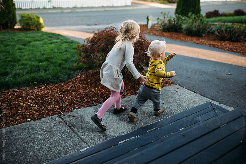Two young siblings run in their front yard by Amanda Voelker for Stocksy United