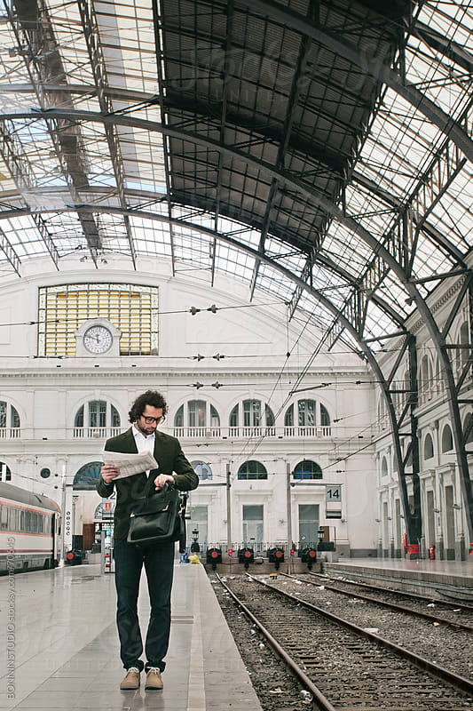 Young businessman holding newspaper checking the time waiting on train station. by BONNINSTUDIO for Stocksy United